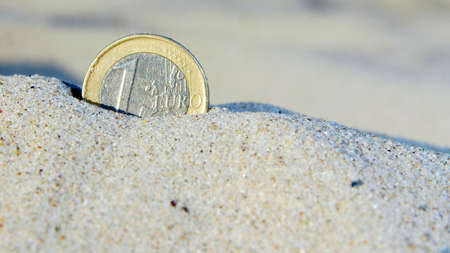 lost money: Euro coin in the sand, lost money