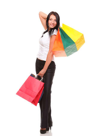 Portrait of young woman carrying shopping bags against white background photo