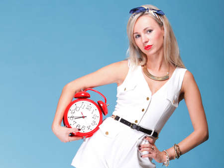 Portrait of pretty young woman in white dress against blue background timer red clock photo