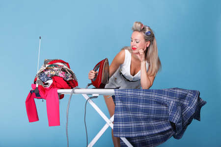 pin up girl retro style portrait woman ironing posing housewife with iron blue background photo