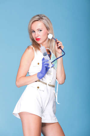 Sexual woman in nurse suit with stethoscope blue background Stock Photo - 15166562