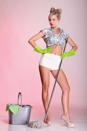 Cheerful pin up girl retro style portrait pinup Woman housewife cleaner mop pink background full lenght