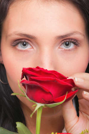 Closeup portrait of an attractive young woman holding a red rose photo