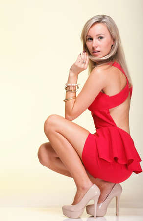 strapless: full lenght Portrait of pretty young woman in red dress against yellow background