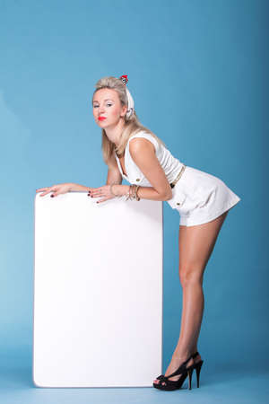 full lenght Beautiful young woman with pin-up make-up and hairstyle posing in studio with white board. Stock Photo - 15232786