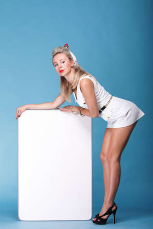 full lenght Beautiful young woman with pin-up make-up and hairstyle posing in studio with white board. photo