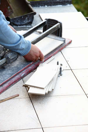 tile cutter: man cutting tile by cutter worker Stock Photo