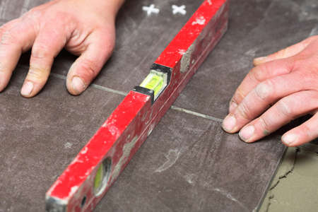 level Construction worker is tiling at home, tile floor adhesive Stock Photo - 15773776