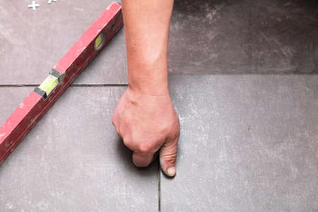 Man Construction worker is tiling at home, tile floor adhesive Stock Photo - 15773837