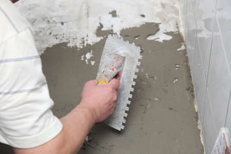 Man Construction worker is tiling at home, tile floor adhesive Stock Photo - 15773602