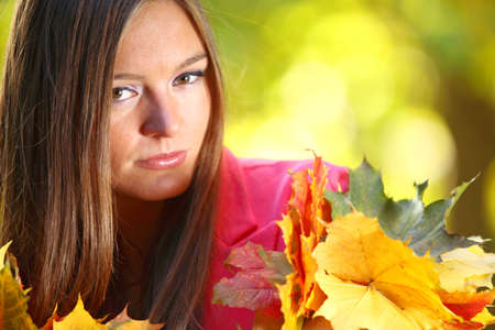 Young woman with autumn leaves in hand and fall yellow maple garden background Stock Photo - 15848957