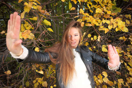 Young woman stand autumn leaves fall yellow green girl garden fend off male assault long hair Stock Photo - 15848940