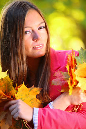 Young woman with autumn leaves in hand and fall yellow maple garden background Stock Photo - 15981226