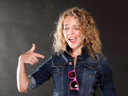 Young beautiful woman with long curly blond hair on grey background photo
