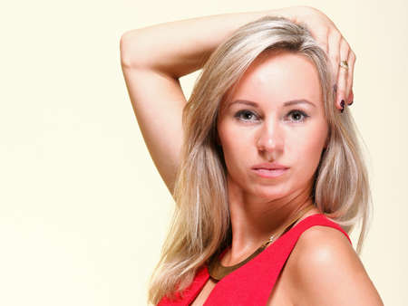 Portrait of pretty young woman in red dress against yellow background photo