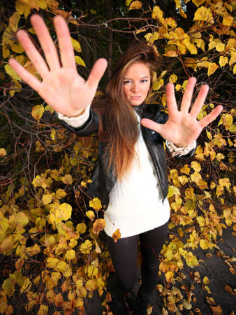 Young woman stand autumn leaves fall yellow green girl garden fend off male assault long hair photo