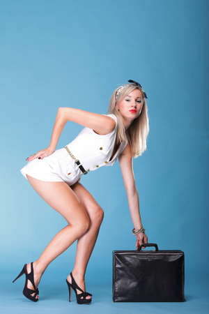 full lenght Portrait of pretty young woman in white dress and black travel bag against blue background photo