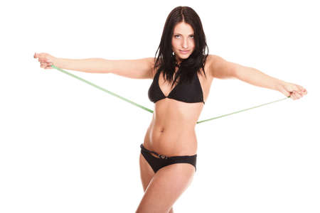 young brunette girl very tiny body in bikini with measuring her waistline a tape photo