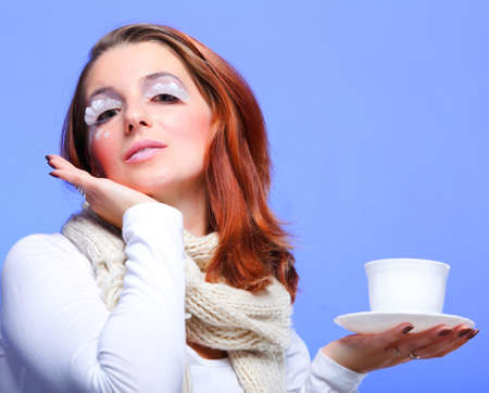 Beautiful winter young woman portrait with white eye-lashes eyelash hat violet and drink tea cup photo
