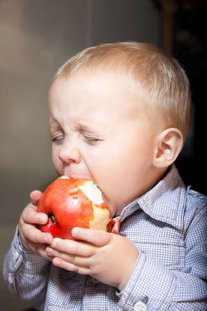Little boy eating apple photo