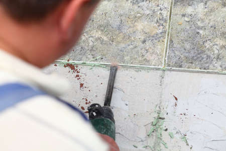 manual worker disassembling old floor tiles photo
