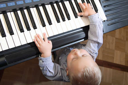 little boy playing piano indoor Stock Photo - 17481391