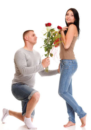 Loving Portrait of beautiful young happy smiling couple isolated - man down on his knee giving his girlfriend a rose and the girl isolated on white photo