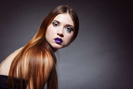 woman straight long hair make-up posing in studio dark background photo