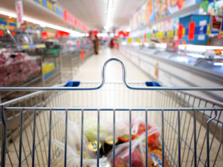 view of a shopping cart with grocery items at supermarket  blurred background photo