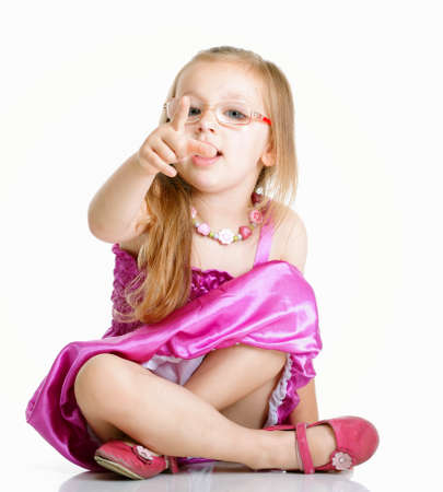 cute little girl glasses sitting on floor pointing you studio shot  isolated on white background photo