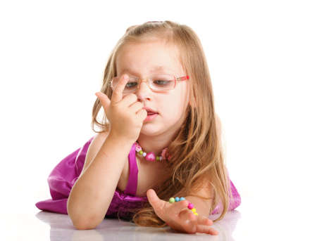 cheerful little girl glasses to count funny is lying isolated on the white background photo