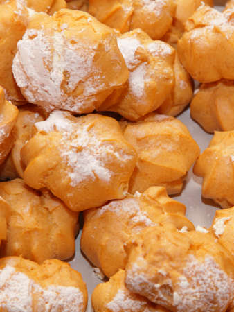 choux bun: profiteroles choux pastry buns with whipped cream as background