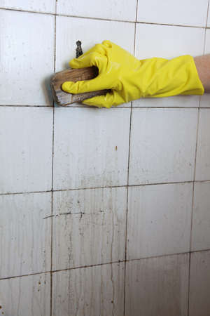gloved hand cleaning dirty old tiles with brush in a bathroom