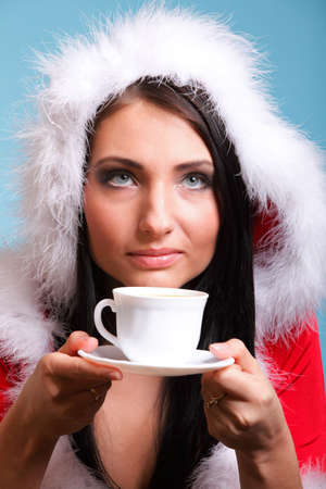 cheerful santa claus woman Girl blowing on hot drink  blue background photo