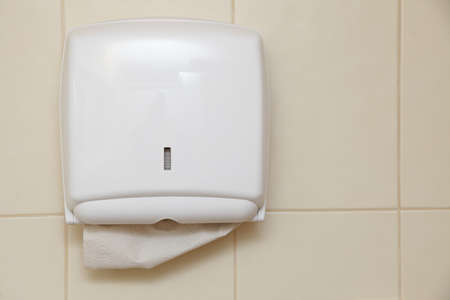 Paper towel dispenser on the wall in the bathroom photo