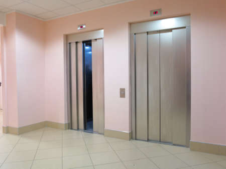 two modern lifts one with opened and another with closed doors photo