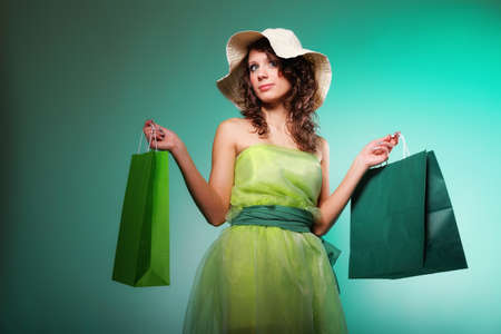 young spring woman with shopping bags on green background photo