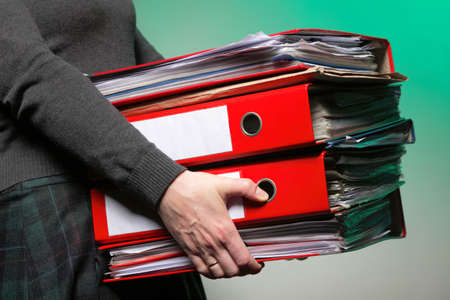 woman in grey holding stack of folders. Pile with old documents and bills on green background photo