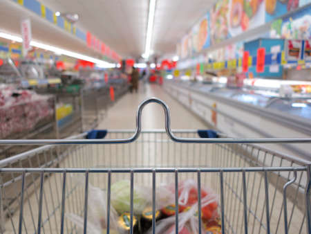 view of a shopping cart with grocery items at supermarket  blurred background