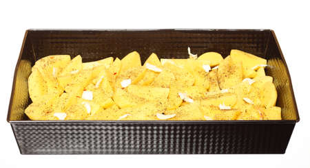 Raw peeled potatoes in tray with spices, butter slices ready to be roasted white background Stock Photo - 18008142