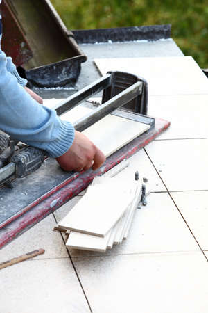 lain: man cutting tile by cutter worker Stock Photo