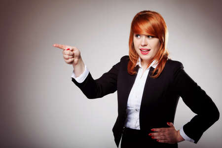 business woman pointing her finger against someone, showing empty copy space. Grey background photo