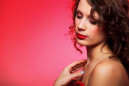 Beautiful young fashion woman with makeup on red background photo