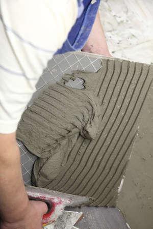 tiler at work bonding of floor  tile adhesive Stock Photo - 18161052