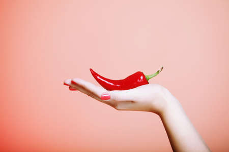 chili pepper in female hand  brown background photo