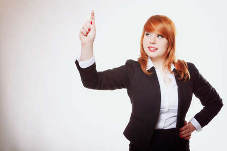 Businesswoman pressing button or something, pointing at the screen. Grey background photo