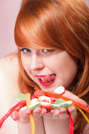 happy young redhair woman with gummy candy multi colored jelly sweets in hands pink background photo