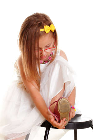 Cute little girl in white dress glasses putting on her own shoes studio shot white background photo