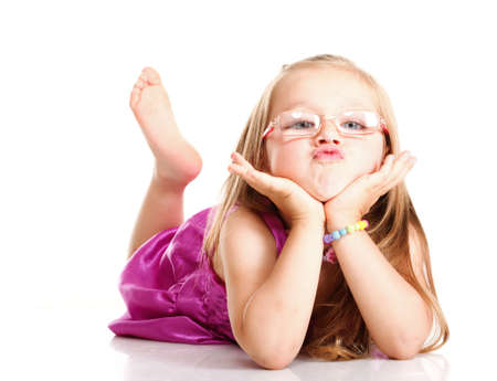 cheerful little girl glasses funny is lying isolated on the white background photo