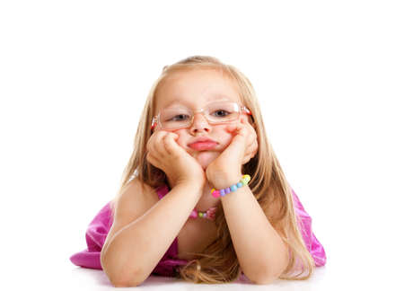 Sad little girl in glasses laying on floor leaning on elbows, chin in hands, looking isolated over white photo